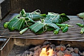 Fish parcels wrapped in banana leaves on the barbecue with vegetables