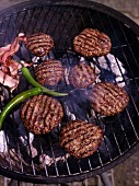Barbecued burgers, chillies and bacon on the barbecue grill