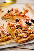 Sliced Barbecue Chicken and Olive Pizza on Parchment Paper