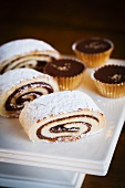 Date Filled Jelly Roll with Chocolate Toffee Candies on a White Platter