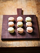 Verschiedene Macarons in drei Reihen auf einem Holzbrett