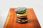 Three Assorted Sandwich Cookies Stacked on a Wooden Board