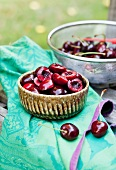 Fresh Cherries; A Bowl of Halved and Pitted Cherries and a Colander of Whole Fresh Ones