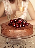 A chocolate layer cake topped with cherries, with a woman holding a glass of sparkling wine in the background