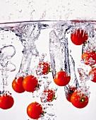 Mehrere Tomaten fallen ins Wasser
