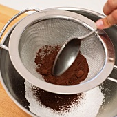 Cocoa being pressed through a sieve for making winter-spiced cream liqueur