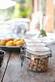 Pistachios in a jar on a wooden table outdoors