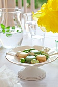 Macaroons and brightly coloured eggs on an Easter table