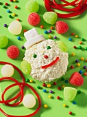 A coconut ball decorated to look like a snowman, with jelly sweets on a green surface