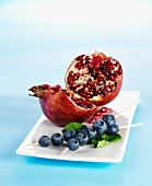 A broken-open pomegranate and skewers of blueberries