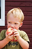 A Young Boy Eating a Peach Outdoors