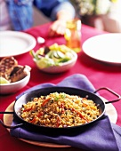 Veggie Paella in a Skillet on a Table; Grilled Steak and Salad in Background
