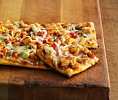 Pizza with curried chicken, peppers and spring onions