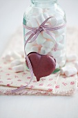 A heart-shaped blackcurrant macaroon and marshmallows in a jar