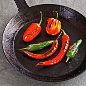 Whole peppers toasted in a pan