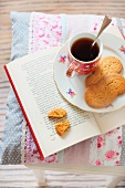 Tea and biscuits on a book on top of a cushion