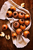 Several medlars on a linen cloth
