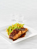 A slice of salmon in teriyaki sauce with vegetables