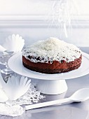 Frozen chocolate dome cake decorated with grated coconut