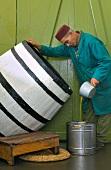 Mann schöpft Olivenöl aus Fass in einen Eimer (Tunesien)