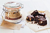 A preserving jar containing the dry ingredients for making brownies, and several brownies