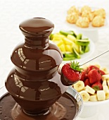 A chocolate fountain with assorted fruit