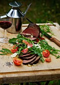 Sirloin of beef with rocket, tomatoes and parmesan at a barbecue