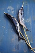 Two skewered fish (mackerel on wooden skewers)