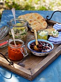 Accompaniments for a barbecue: olives, flatbread, feta and sauces (Greece)