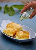 Galaktobouriko (semolina pudding in filo pastry, Greece) being drizzled with syrup