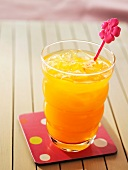 Orange juice with ice and a pink decoration