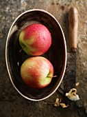 Two Pink Lady apples in a dish