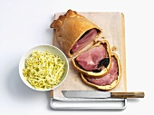 Rolled ham wrapped in pastry with a cabbage salad