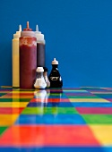 Sauces, salt and pepper pots and seasoning on a colourful restaurant table