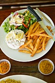 Skinny fries, salad and a poached egg on a plate in a restaurant