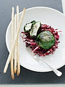 Goat's cheese wrapped in spinach on a bed of red endive, with grissini breadsticks