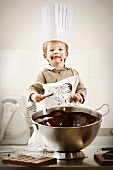 A boy with a chef's hat standing in front of a bowl of melted chocolate