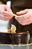 A pastry chef decorates a chocolate tart