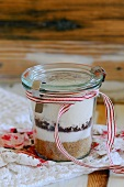 A preserving jar containing the dry ingredients for chocolate biscuits