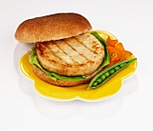 Chicken burger garnished with a fresh pea pod