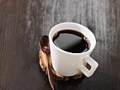 Black coffee in a mug on a disc of wood