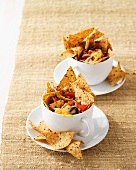 Wholemeal tortilla chips with linseeds in tomato and cheese dip