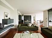 Runder Couchtisch auf flokatiartigem Teppich und grüne Couchgarnitur in Loungeecke mit zwischen Wand eingespanntem Regalboden in offenem Wohnraum