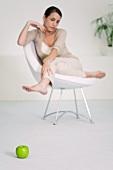 Frau auf einem Stuhl betrachtet grünen Apfel