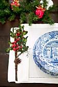 Gedeck mit Blau-weißem Geschirr auf Hohlsaum-Set und kleines Gebinde mit Zapfen und roten Beeren als weihnachtlicher Tischschmuck