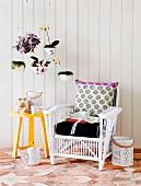 Weisser Rattansessel mit Polstern neben gelb lackiertem Beistelltisch vor weisser Holzwand und von Decke abgehängte Blumentöpfe