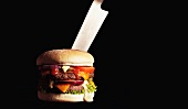 Hamburger stabbed with large kitchen knife/ fatty/ fast food
