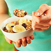 A woman holding a bowl of muesli with banana