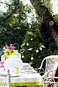 Set terrace table with colourful bouquet and white lantern; decorated Christmas tree in background