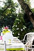Gedeckter Terrassentisch buntem Blumenstrauss und weissen Laternen; im Hintergrund ein geschmückter Christbaum